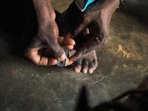 Babalawo-Priester führt ein Ifâ-Orakel durch. Für das Orakel werden Zähennägel des Fragenden verwendet. Ouida, Benin.